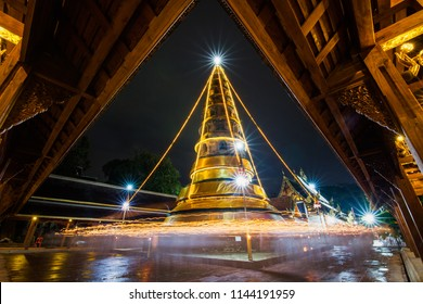 Walk with light candle around pagoda temple at night.