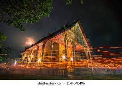 Walk with lighted candles in hand around at a temple