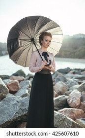 Walk on the sea. Elegant lady is breating fresh air on the coast. She is wearing pink blouse and holding a umbrella.