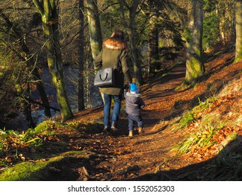 Walk over the waterfall.  Alyth, Blairgowrie, Scotland - February 15, 2019 A young mother walks with her son on a path over the Reekie Linn Waterfall in Scotland.