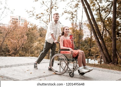 Walk in park. Cheerful wheelchair girl drinking hot coffee and smiling while spending time in the park with positive boyfriend