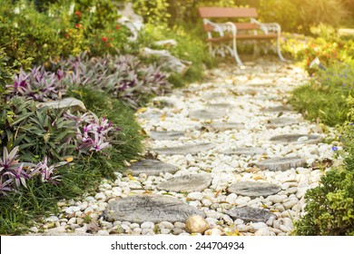 Walk path in garden decorated with stumps and stone to art bench.