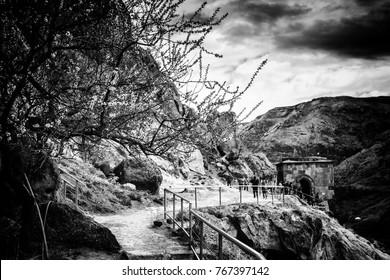 Walk path Vardzia cave city-monastery. Vardzia was excavated in the Erusheti Mountain on the left bank of the Kura River, thirty kilometres from Aspindza,  Georgia in black and white dramatic style
