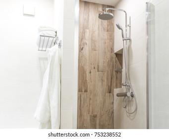 Walk in shower in bathroom with wooden style tile, glass door and hanging bathrobe