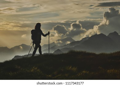 Walk in solitude on the Alps. A woman on with the background of abstract mountains in the clouds.