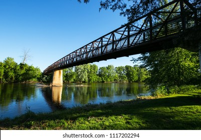 Walk way bridge with a reflection of a tree line on the Grand River in Ionia Michigan State Park in late spring