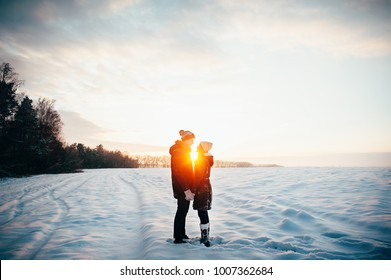 Walk in winter. Young people, a guy and a girl are kissing at sunset on a snow-covered field. Love story.