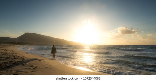 Walk of a woman on the island of Sardinia; Sunset on the Mediterranean