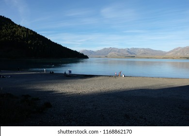 A walker looks out across Lake Tekapo in New Zealand on a sunny day in Autumn.