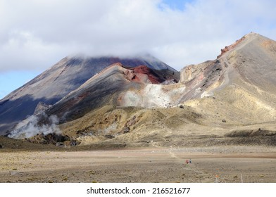 Walkers crossing the volcanic landscape of Tongariro National Park, New Zealand, showing the Red Crater and Mount Ngauruhoe.