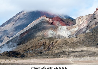 Walkers on the Tongariro Crossing, New Zealand, with dramatic view across Red Crater to Mount Ngauruhoe.