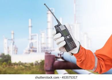 walkie-talkie radio in hand distillation background. comunication in refinery process