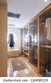Walk-in closet in wood and marble with large round lighted window. Nobody inside
