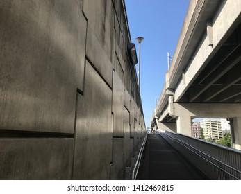 walkin' the sidewalk under the bridge between gray walls