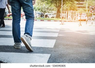 Walking across the crosswalk.Men wear jeans.