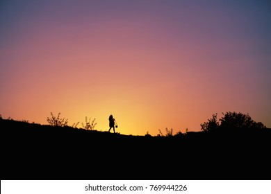 Walking alone (lonely) woman (girl) with bag silhouettes on pink yellow violet purple lilac sunset time today