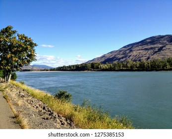 Walking along the paths of the North Thompson river in Kamloops, British Columbia, Canada on a beautiful sunny fall day.  The river is a pristine turquoise colour and there is a small mountain behind.