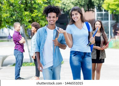 Walking american young adult student and latin hipster student outdoor in summer