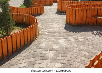The walking area is surrounded by a decorative wooden fence of curved shape. Paved with tiles of different shapes.