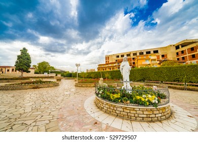 Walking around buildings of  Medjugorje, statue of the Blessed Virgin Mary