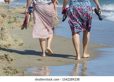 Walking barefoot. Barefooted female legs. Walk on the wet sand. Walk along the sea. Without shoes. Feeling of freedom. Departing people. Two women or girls. Wet drumsticks.
