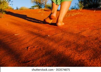 walking barefoot on red sand dune at sunset  Lasseter Highway near - Kata Tjuta National Park in Central Australia