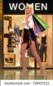Walking beautiful, young woman at the mall, with shopping bags, over lingerie shop window as a background