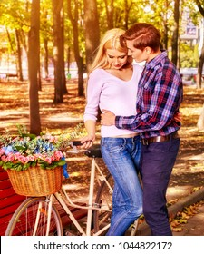 Walking bike of couple in park and kissing. Summer friends walk outdoor. First date of two young people in good weather day. Sun backlight on background. Love at first sight. Sun flare first love of