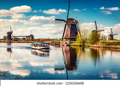 Walking boat on the famoust Kinderdijk canal with windmills. Old Dutch village Kinderdijk, UNESCO world heritage site. Netherlands, Europe.