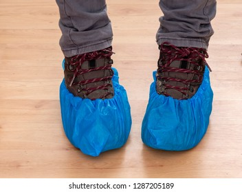 Walking boots and feet in blue plastic shoe protectors, covers. Hygiene in medical situations etc. Single use, disposable.