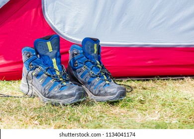 Walking boots with socks beside a tent on a campsite