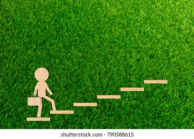 Walking Business concept the stairs walks up to the goal to succeed paper cut of a green background