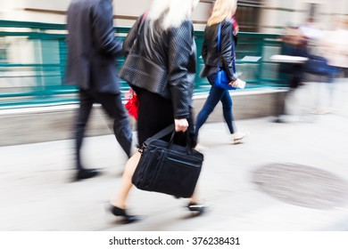 walking business people in the city in motion blur