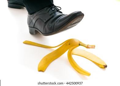 Walking businessman is going to slip on banana peel.
