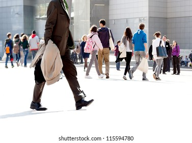 Walking businessman. A group of young people and businessmen walking on the background of the urban landscape. Urban landscape.