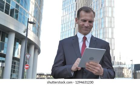 Walking Businessman Using Tablet, Outside Office