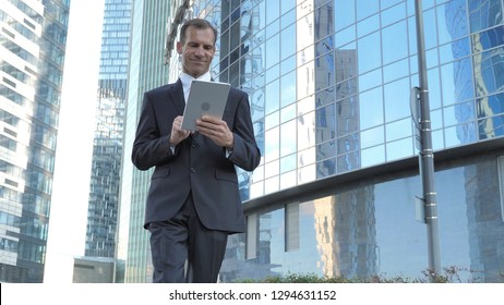 Walking Businessman Using Tablet while Walking Outside Office