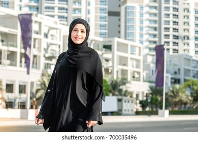 Walking businesswoman looking in the camera and smile. Arab woman dressed in abaya.