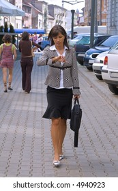 Walking businesswoman while she is checking the time