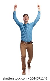 walking casual man celebrting success with hands in the air on white background