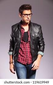 walking casual man in leather jacket is looking to his side on gray background
