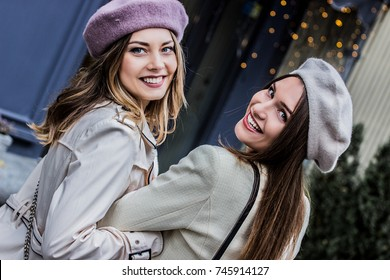 Walking the city with best friend. Back view of two beautiful french women in berets looking back to camera and smiling while walking together outdoors. Friendship concept.