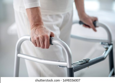 Walking disability. Close up of a female hand holding on to the walker while trying to walk