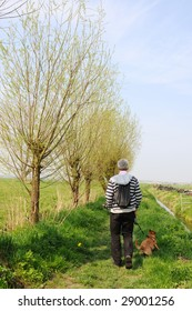 walking the dog with backpack in typical Dutch landscape