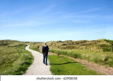 Walking the dog in coast landscape with sand dunes at Ameland