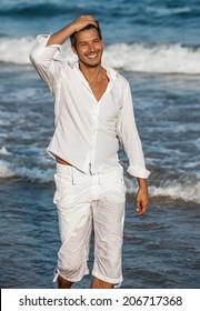 walking down the seaside beach smiling