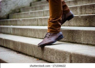 Walking downstairs: close-up view of man's leather shoes