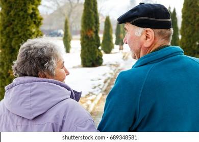 Walking elderly couple in the park in wintertime