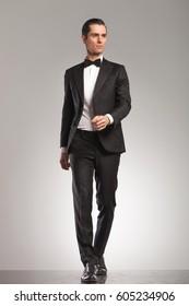 walking elegant man in tuxedo is looking up to side on grey studio background