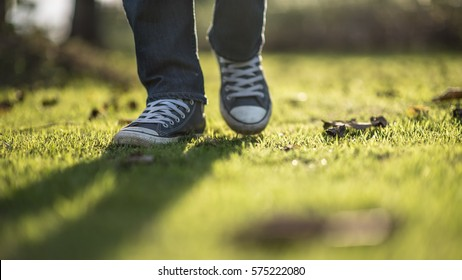 Walking feet ; Man wear blue jean and canvas sneaker sunrise walking on sunrise lawn and landscape background.